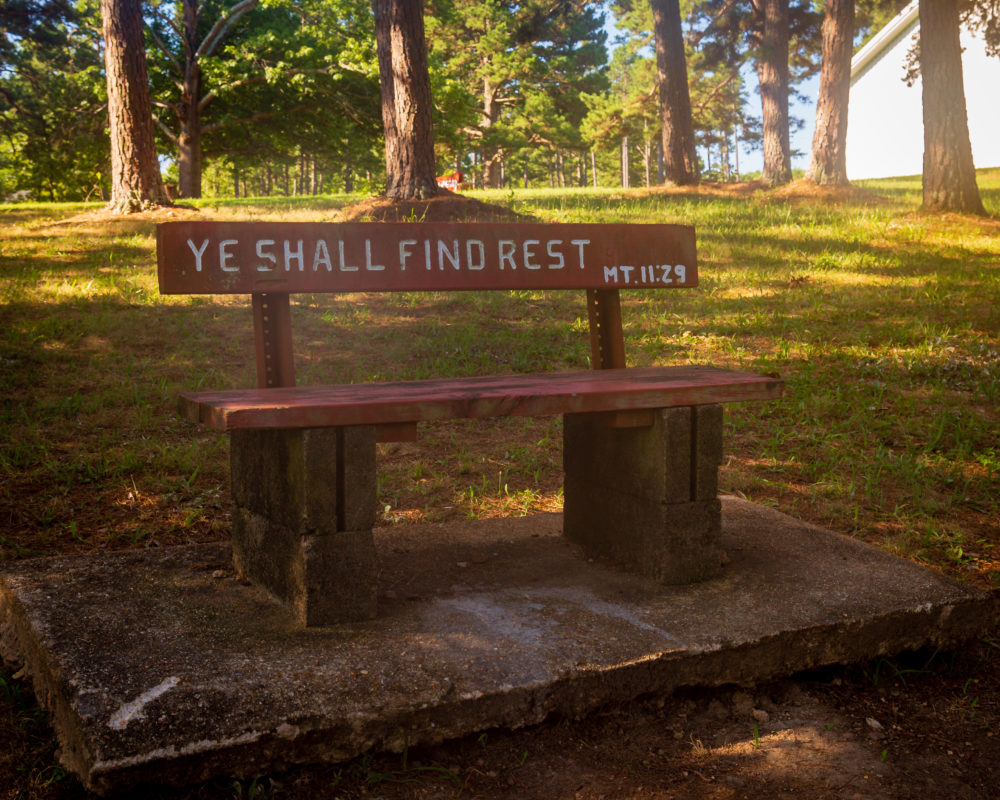 """A wooden bench in a tree lined park at Missionary Acres that reads """"Ye Shall Find Rest."""""""