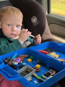 Our young son playing with a container of Legos in the car. These help make traveling with kids go smoothly.